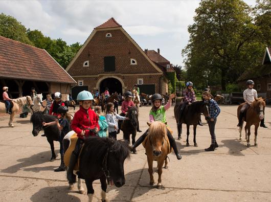 Kinder auf Pferden im Hof